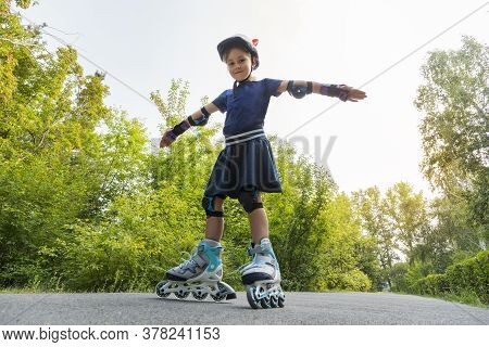 Little Girl On Roller Skates At A Park. A Child Rides On Roller Skates With His Arms Outstretched Ag