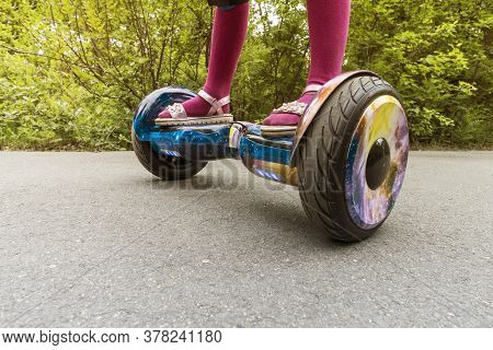 Legs Of Girl Riding On Self-balancing Mini Hoverboard In City Park. Electronic Scooter Outdoors - Pe