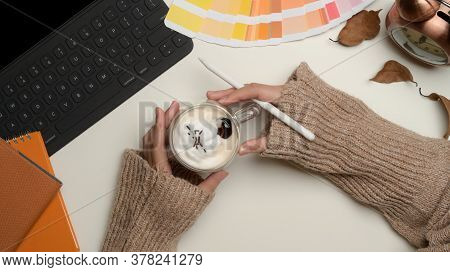 Female Designer Hands Holding A Cup Of Beverage On Worktable With Supplies In Home Office Room