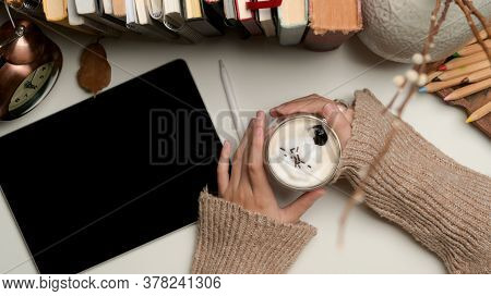 Female Hands Holding A Cup Of Beverage On Worktable With Tablet, Books And Decorations