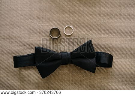 Close-up Of A Black Bow Tie And Two Wedding Rings On A Gray Background.