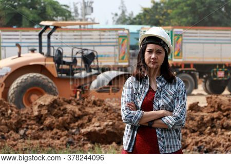 Female Civil Engineer With White Helmet, Standing And Hugging Chest With Loader Pedal Car And Pile O