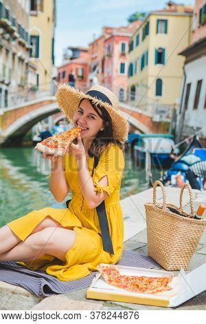Woman Sitting On Pond With View Of Venice Canal Eating Pizza