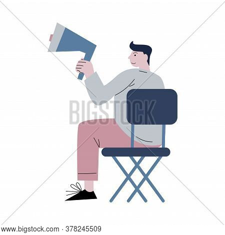 Film Director Sitting And Giving Commands Into Loudspeaker During Cinema Production