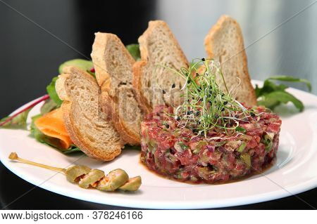Raw Meat Tartare For Gourmet Meat. Raw Tartar Meat With Spices, Croutons And Herbs. Beef Tartar With