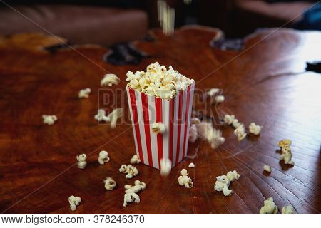 Popcorn Flying Out Of Cardboard Box. Red And White Striped Popcorn Bucket With Flying Popcorn In The