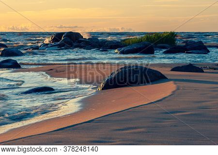Waves With Splashes On The Sandy Beach Of The Baltic Sea With Large Stones In A Storm At Sunset. Wav