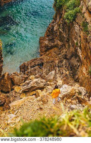 Woman In Yellow Raincoat Hiking To Sea Beach At Canyon
