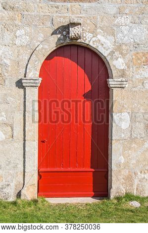 Red Wooden Door Of Notre Dame De Bon Voyage Chapel In Plogoff