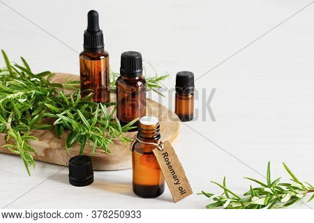 Rosemary Essential Oil And Fresh Rosemary Branch On Wooden Background.