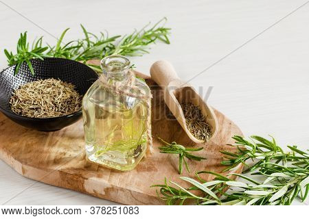 Bottle Rosemary Infused Oil And Fresh Rosemary Branch On White Wooden Background.