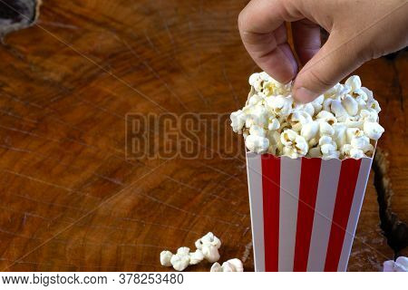 Hand Taking Popcorn Out Of Red And White Striped Cardboard Bucket Retro Design On Wooden Table