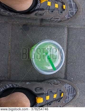 Top View On Plastic Cup With Greenish Liquid (mojito) And Cocktail Tube Inside, Standing On Pavement