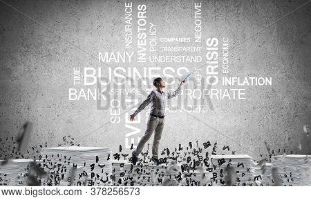 Man In Casual Wear Keeping Hand With Book Up While Standing Among Flying Letters With Business-relat