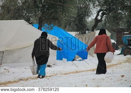 Aleppo, Syria 15 February 2017\na Refugee Woman Holds A Bucket Of Water On Her Head During The Snow