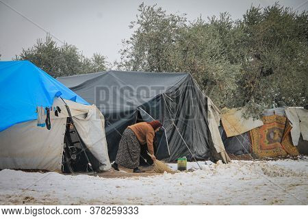 Aleppo, Syria, February 15, 2017 A Woman Cleans The Perimeter Of The Tent Where She Lives In The Sno