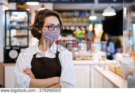 Young Waitress With Face Mask Standing In Cafe, Arms Crossed.