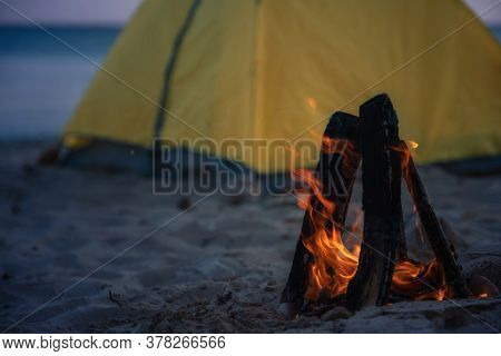 Closeup Fire In Bonfire In The Beach . Camping And Tents To Travel. Night Camping On Sea Shore.