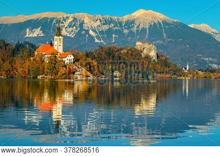 Autumn Landscape With Lake Bled. Cute Pilgrimage Church On The Shore Of Lake And Spectacular Fortres