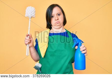 Brunette woman with down syndrome wearing apron holding scourer and toilet brush clueless and confused expression. doubt concept.