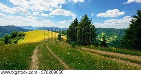 Rural Landscape On A Summer Day. Dirt Road In The Grassy Fields And Rolling Hills. Fluffy Clouds On
