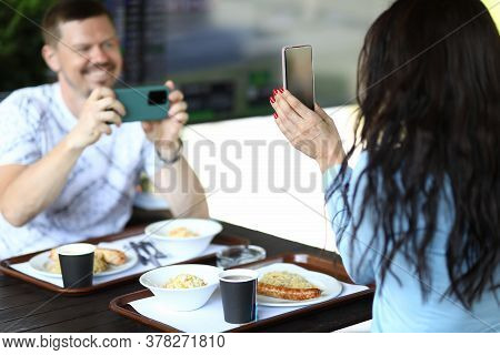 Woman Is Holding Smartphone In Her Hands, Man Is Filming Review Of Novelty On Smartphone In Cafe. Te