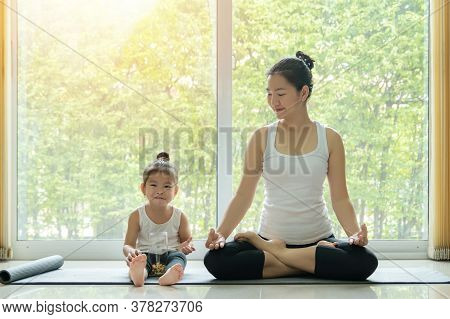 Asian Mother Practiced Yoga By Sitting In Lotus Position At Home With A Daughter Sitting Beside And