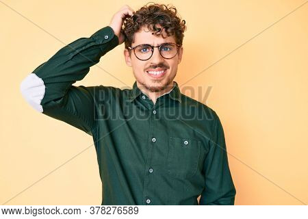 Young caucasian man with curly hair wearing casual clothes and glasses confuse and wonder about question. uncertain with doubt, thinking with hand on head. pensive concept.