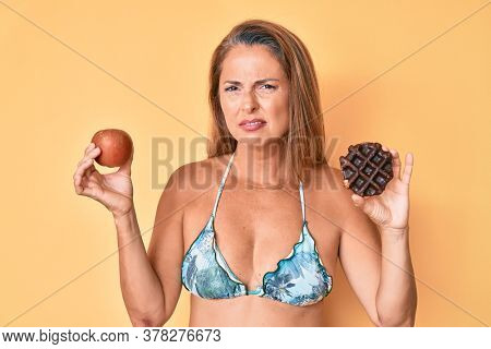 Middle age hispanic woman holding apple and donut clueless and confused expression. doubt concept.