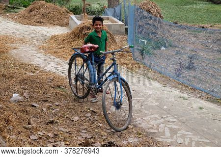 KUMROKHALI, INDIA - FEBRUARY 24, 2020: Portrait of a boy with a bicycle, Kumrokhali, West Bengal, India
