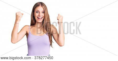 Young beautiful blonde woman wearing casual style with sleeveless shirt screaming proud, celebrating victory and success very excited with raised arms
