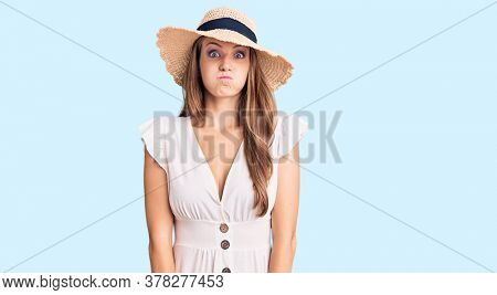 Young beautiful blonde woman wearing summer dress and hat puffing cheeks with funny face. mouth inflated with air, crazy expression.