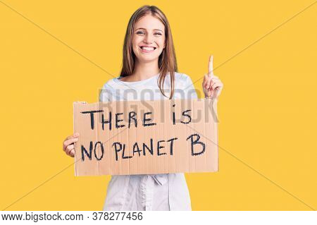 Young beautiful blonde woman holding there is no planet b banner surprised with an idea or question pointing finger with happy face, number one
