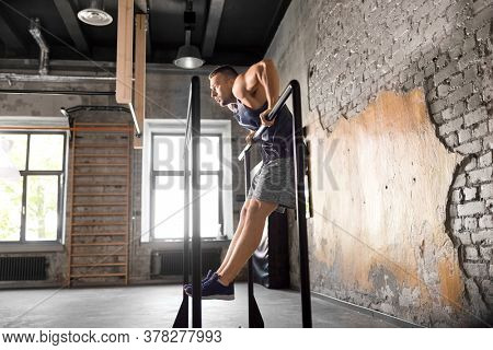 fitness, sport, bodybuilding and people concept - young man doing push-ups on parallel bars in gym