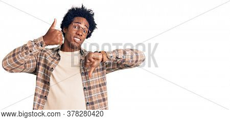 Handsome african american man with afro hair wearing casual clothes and glasses doing thumbs up and down, disagreement and agreement expression. crazy conflict