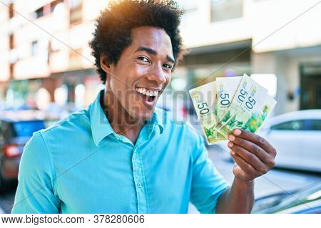 Young african american man smiling happy. Standing with smile on face holding israeli shekels banknotes at town street.