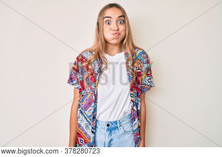 Young beautiful blonde woman wearing modern clothes puffing cheeks with funny face. mouth inflated with air, crazy expression.