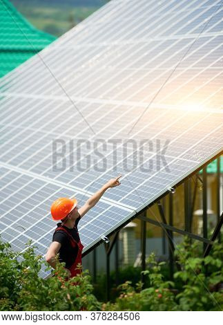 Man Worker In An Orange Helmet Pointing At A High Solar Station On A Plot Of Land With Greenery. Alt