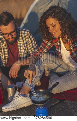 Couple In Love On An Outdoor Camping Adventure, Making Dinner At A Lake Docks And Enjoying A Beautif