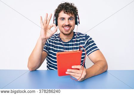 Young caucasian man with curly hair using touchpad sitting on the table doing ok sign with fingers, smiling friendly gesturing excellent symbol