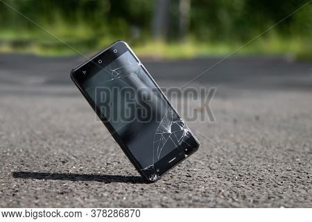 Broken Phone Screen On Asphalt. Dropped Mobile Phone On The Ground And Smashed The Screen. Falling S