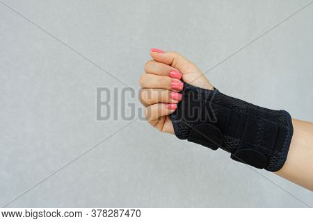 Close Up Of Woman's Hand Wearing Supportive Orthopedic Wrist Brace In And Copy Space