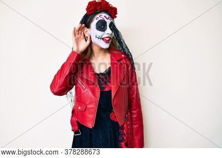 Woman wearing day of the dead costume over white smiling with hand over ear listening an hearing to rumor or gossip. deafness concept.