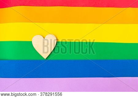 Wooden Heart On Lgbtq Flag Background, Top View, Copy Space For The Text