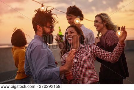 Happy Young Men And Women Laughing And Enjoying Life While Dancing On Rooftop During Rooftop On Suns