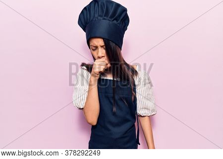 Beautiful child girl wearing cooker uniform feeling unwell and coughing as symptom for cold or bronchitis. health care concept.