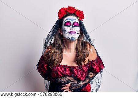 Young woman wearing day of the dead costume over white smiling and laughing hard out loud because funny crazy joke with hands on body.