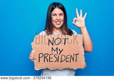 Young beautiful woman on disagreement holding banner with not my president message doing ok sign with fingers, smiling friendly gesturing excellent symbol