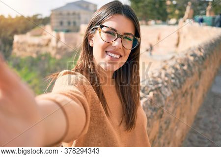 Young beautiful brunette woman wearing glasses smiling happy and confident. Standing with smile on face making selfie by the camera at street of city