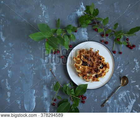 Waffles On A Light Ceramic Plate On A Gray Background With Laid Out Sprigs Of Red Bird Cherry